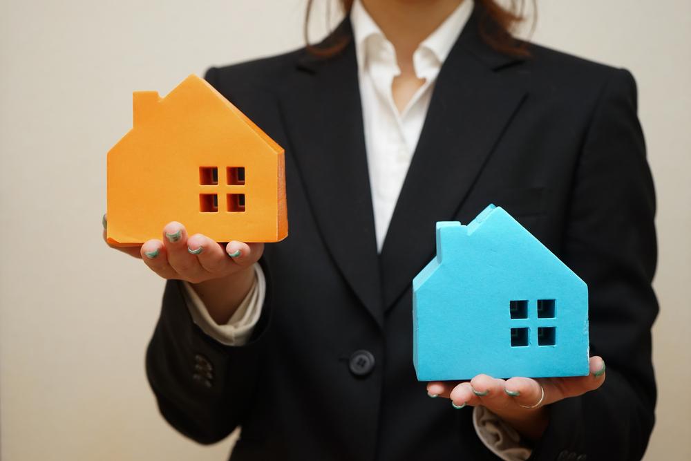 2つの家の模型を持っている女性
